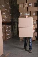 trabalhador com caixas no armazém foto