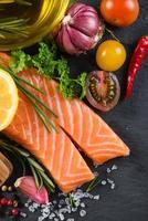 porção de salmão fresco com especiarias, ervas e vegetais foto