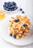 waffles frescos com mirtilos, mesa de café com xarope de bordo foto