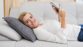 loira linda usando tablet no sofá