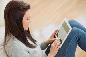 menina usando um tablet sentada no chão