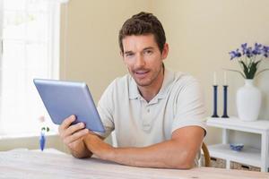 homem sorridente usando tablet digital em casa