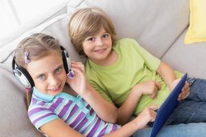 irmãos usando tablet digital enquanto ouvem música no sofá