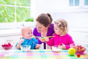 mãe e filhos tomando café da manhã foto
