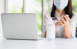 frasco de álcool gel com uma mulher usando máscara lavando a mão