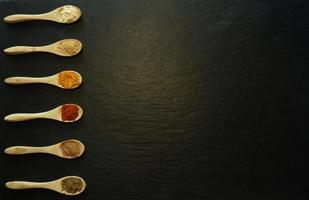 especiarias em pó em pequenas colheres de madeira foto