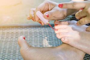 mulher pintando as unhas dos pés