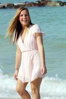 jovem caminhando nas ondas na praia