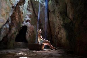 garota na caverna sob os raios do sol foto