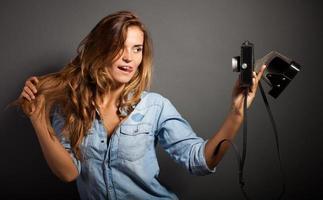 Mulher fotógrafa boba tirando fotos dela mesma câmera velha