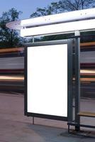 ponto de ônibus com quadro de anúncios à noite