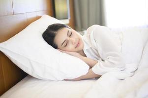 bela jovem dormindo em sua cama foto
