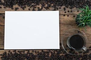 papel em branco e grãos de café na mesa