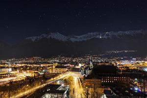 vista noturna sobre a cidade de innsbruck com a cadeia de montanhas foto