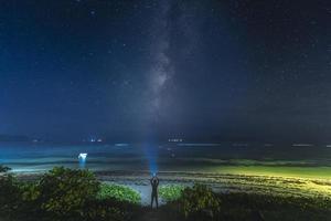 pessoa em pé com luz estroboscópica sob a Via Láctea