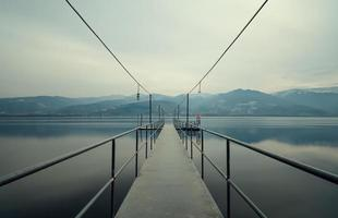 ponte de pé de metal que leva ao lago