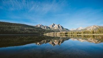 montanhas e reflexo da floresta em um lago