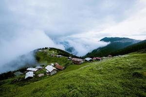 pequena vila em montanhas verdes gramadas