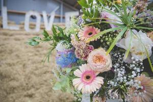 close-up em um buquê de flores coloridas em tons pastel com cartas de amor ao fundo