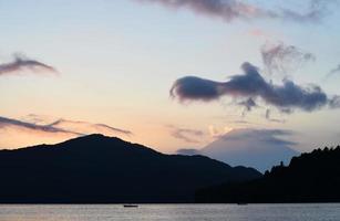 água em silhueta e montanhas durante o pôr do sol foto