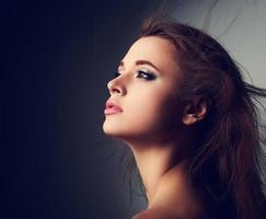 Perfil de mulher bonita maquiada com cabelo comprido olhando para cima
