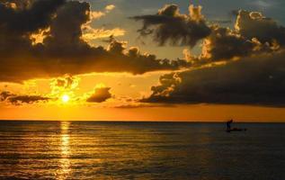 silhueta de pescador pescando ao pôr do sol foto