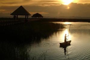 Punt de aldeão tailandês no lago, no pôr do sol. foto