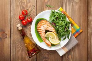 salmão grelhado, salada e condimentos na mesa de madeira