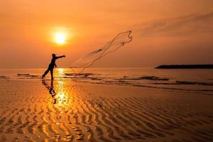 pescador jogando rede ao pôr do sol.