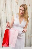 mulher loira abrindo uma sacola de presente enquanto olha para a câmera