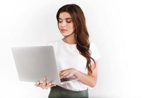 mulher vestida com estilo empresarial trabalha em laptop em fundo branco foto