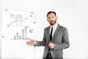 homem vestido com terno de escritório discute gráfico em quadro branco foto