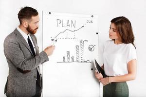 empresário e mulher debatem sobre gráfico no quadro branco foto