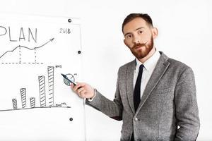 homem vestido com terno de escritório escreve no gráfico em um fundo branco foto