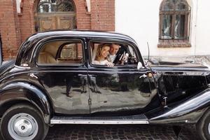 casal de noivos elegantes sorrindo em carro retrô foto