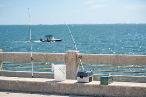 varas de pesca e caixas de equipamento em um píer foto