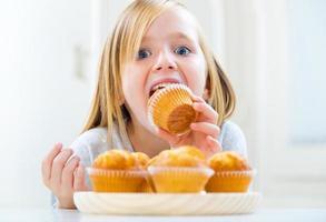 criança linda tomando café da manhã em casa.