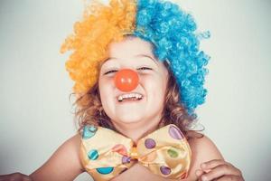 menina sorridente com peruca de palhaço e nariz de palhaço