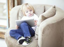 criança linda brincando com o tablet no sofá foto