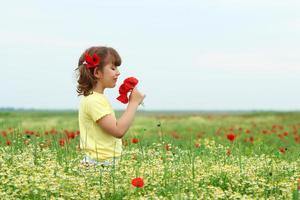 linda garotinha com flores de papoula na primavera