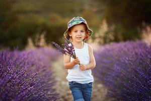 adorável menino fofo com um chapéu em um campo de lavanda