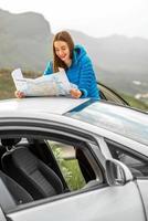 viajante com mapa turístico perto do carro