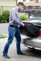 homem colocando bagagem no porta-malas do carro