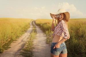 linda garota com câmera retro em uma estrada rural, instagra