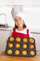 criança orgulhosa e feliz apresentando bolos de muffin e aprendendo a cozinhar