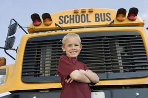 estudante do ensino fundamental parado perto do ônibus escolar foto