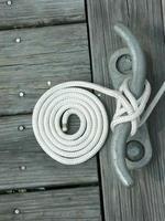 corda branca enrolada em cais de madeira