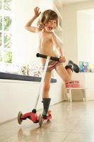 menino andando de scooter dentro de casa de cueca