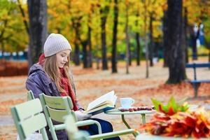 menina lendo um livro em um café ao ar livre foto