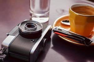 xícara de café vazia e câmera retro foto